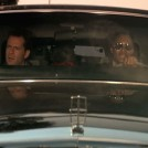 John McClane sitting up front in the Limo with Argyle - Die Hard