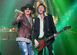 "LAS VEGAS, NV - MAY 21: Singer Axl Rose (L) and bassist Tommy Stinson of Guns N' Roses perform at The Joint inside the Hard Rock Hotel & Casino during the opening night of the band's second residency, ""Guns N' Roses - An Evening of Destruction. No Trickery!"" on May 21, 2014 in Las Vegas, Nevada. (Photo by Ethan Miller/Getty Images)"